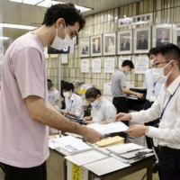 A foreign resident receives a vaccine passport in Tokyo's Shinagawa Ward on July 29. | KYODO