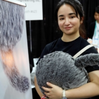 Saaya Okuda of Yukai Engineering holds a Qoobo therapeutic robot, a cushion with a tail that moves depending on how it is caressed, at CES Unveiled in Las Vegas, in January 2020. | REUTERS