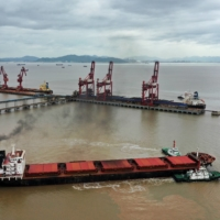 A bulk carrier leaves Ningbo-Zhoushan port with the assistance of tugboats.   REUTERS