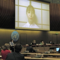 Participants listen to an online video speech by Japanese teenager Rio Sasaki during a U.N. disarmament conference session in Geneva on Thursday. | KYODO