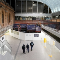 Police officers patrol through the quiet Central Station in the city center during a lockdown to curb the spread of COVID-19 in Sydney on Thursday.  | REUTERS