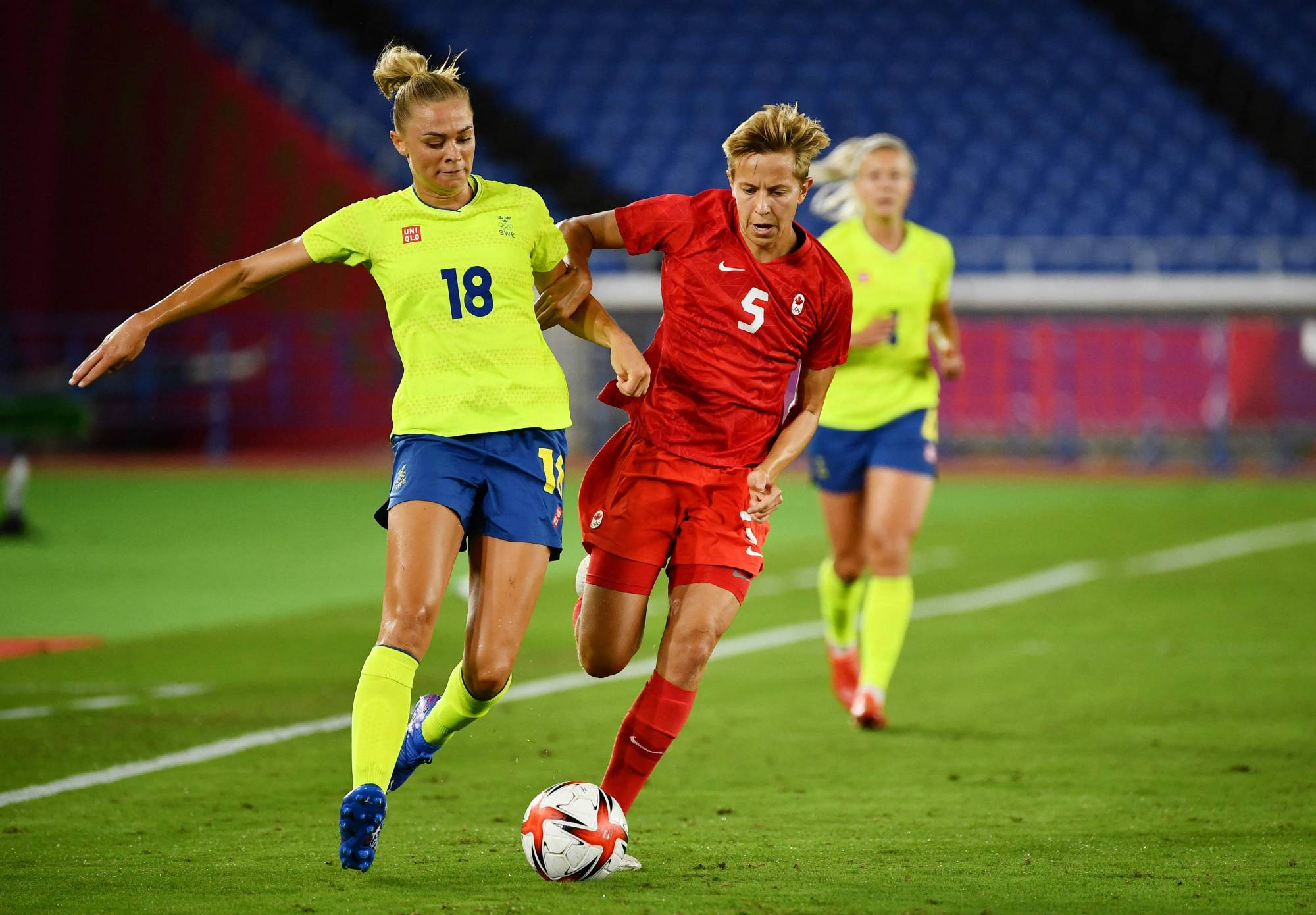 Canadian midfielder Quinn (right) and Sweden's Fridolina Rolfo fight for the ball during the women's soccer final at the Tokyo Olympics on Aug. 6. | AFP-JIJI