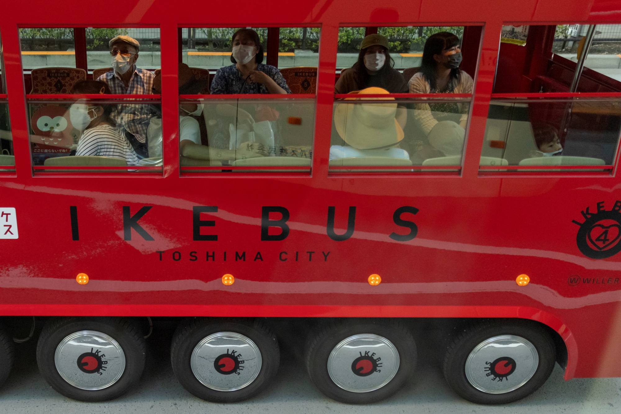 People ride on a tourist bus in Tokyo on July 21. | REUTERS