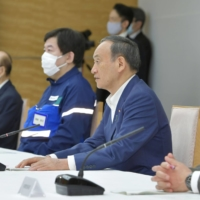 Prime Minister Yoshihide Suga speaks at a meeting of ministers Friday.   KYODO