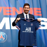 Lionel Messi poses for photos during his introductory news conference with Paris St. Germain in Paris on Aug. 11. | REUTERS