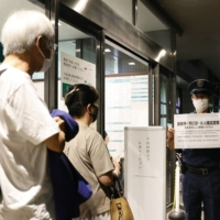 People wait for a COVID-19 vaccination at Fukuoka City Hospital, which is offering 24-hour vaccinations, in July.    KYODO
