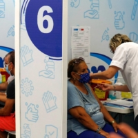 Israelis receive a dose of the Pfizer-BioNtech COVID-19 vaccine, at the Maccabi Health Service in the Israeli town of Rishon Lezion on Friday, as the country launches its campaign to give booster shots to people aged over 50, in a bid to stem spiking infections driven by the delta variant.