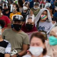 Residents line up to receive cash assistance from the government following the imposition of two-week lockdown to prevent the spread of the coronavirus delta variant in Manila last week. | REUTERS