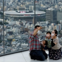A family takes a selfie in Tokyo on Aug. 7. | REUTERS