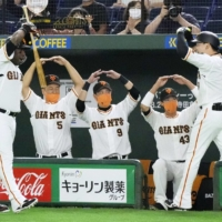 Giants players welcome Yoshihiro Maru (right) back to the dugout after his first-inning home run on Saturday at Tokyo Dome. | KYODO