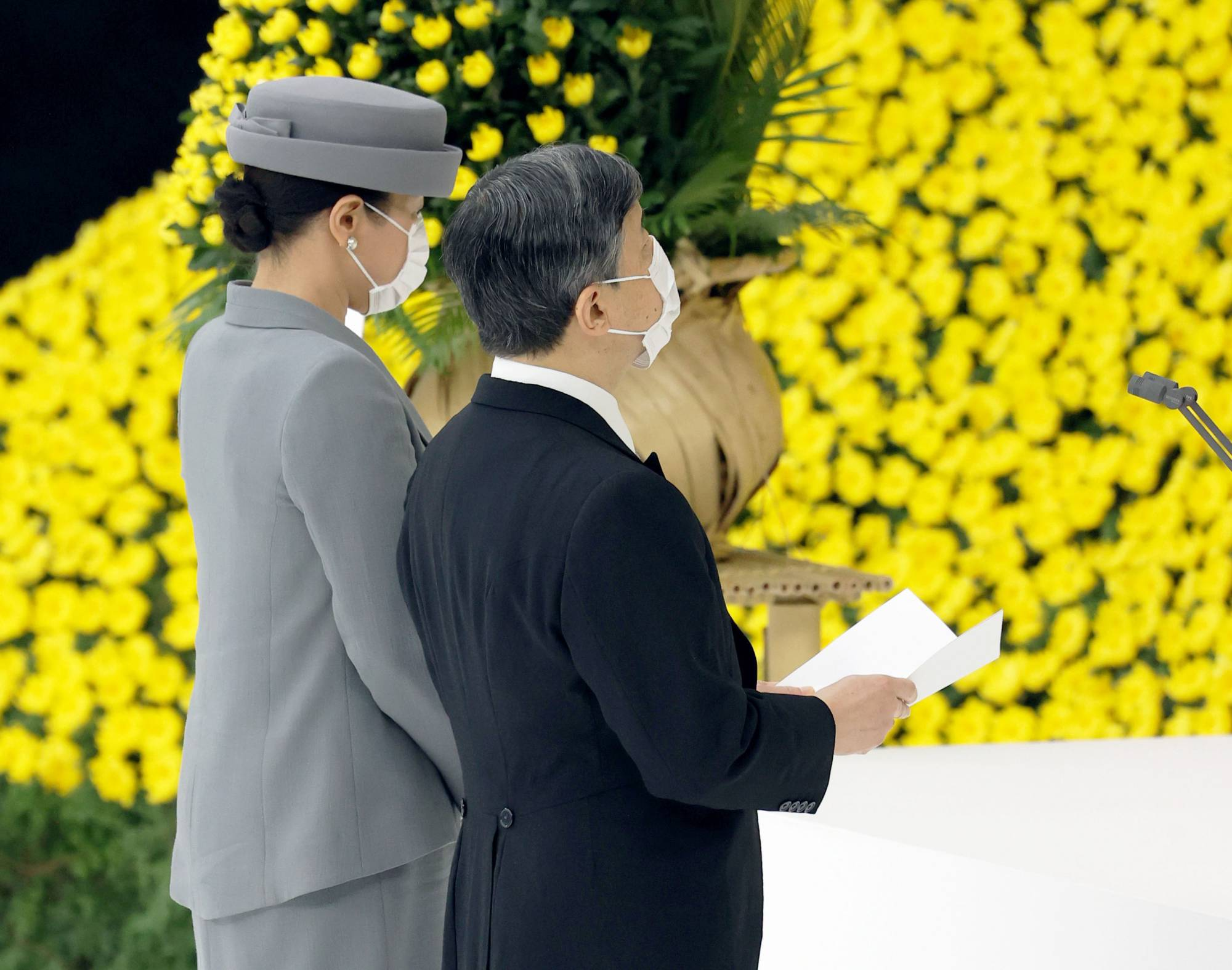 Emperor Naruhito (right) delivers remarks as he and Empress Masako attend a memorial ceremony marking the 76th anniversary of Japan's surrender in World War II held at Nippon Budokan hall in Tokyo on Sunday. | POOL / VIA KYODO