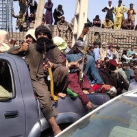 Taliban fighters sit on a vehicle along a street in Afghanistan's Jalalabad province on Sunday. | AFP-JIJI