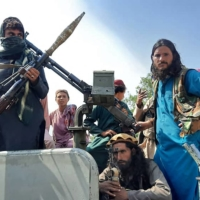 Taliban fighters sit on a vehicle on a street in Afghanistan's Laghman province on Sunday. | AFP-JIJI