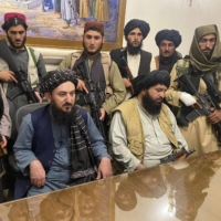 Taliban fighters sit inside Afghanistan's presidential palace in Kabul on Sunday. | AP / VIA KYODO