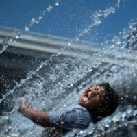 A girl plays in the fountain at Georgetown Waterfront Park during a heat wave on Friday in Washington. | AFP-JIJI