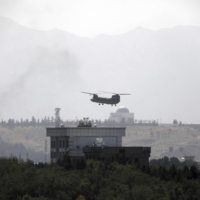 A U.S. helicopter flies above the American Embassy in Kabul as the Taliban reached the gates of the Afghan capital on Sunday. | AP / VIA KYODO