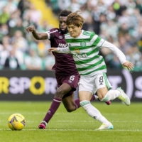 Kyogo Furuhashi (right) of Celtic vies for the ball during the second half of a game against Hearts in Glasgow on Sunday. | KYODO