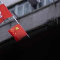 The flags of Hong Kong and China hang above a street in the city on Sunday.    AFP-JIJI