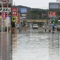 A road is submerged due to heavy rain in Takeo, Saga Prefecture, on Sunday. | KYODO