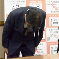 Nagoya Mayor Takashi Kawamura apologizes during a news conference on Monday for biting an Olympic softball player's gold medal earlier this month. | KYODO
