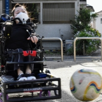 Mari Nagaoka, a power wheelchair soccer player in Yokohama, practices alone in the summer heat at her local park, as the pandemic has forced her team to stop training together at a gymnasium.   TOMOHIRO OSAKI