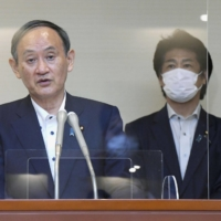 Prime Minister Yoshihide Suga speaks to reporters in Tokyo on Monday, as health minister Norihisa Tamura stands behind him.   POOL / VIA KYODO