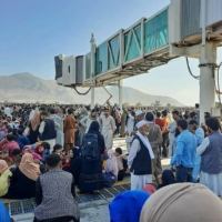 Afghans crowd the tarmac at Hamid Karzai International Airport in Kabul on Monday as they attempt to flee the country. | AFP-JIJI