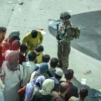 U.S. soldiers stand guard as Afghan people wait at the Kabul airport in Kabul on Monday, as thousands of people mobbed the city's airport trying to flee the Taliban's feared hardline brand of Islamist rule.  | AFP-JIJI