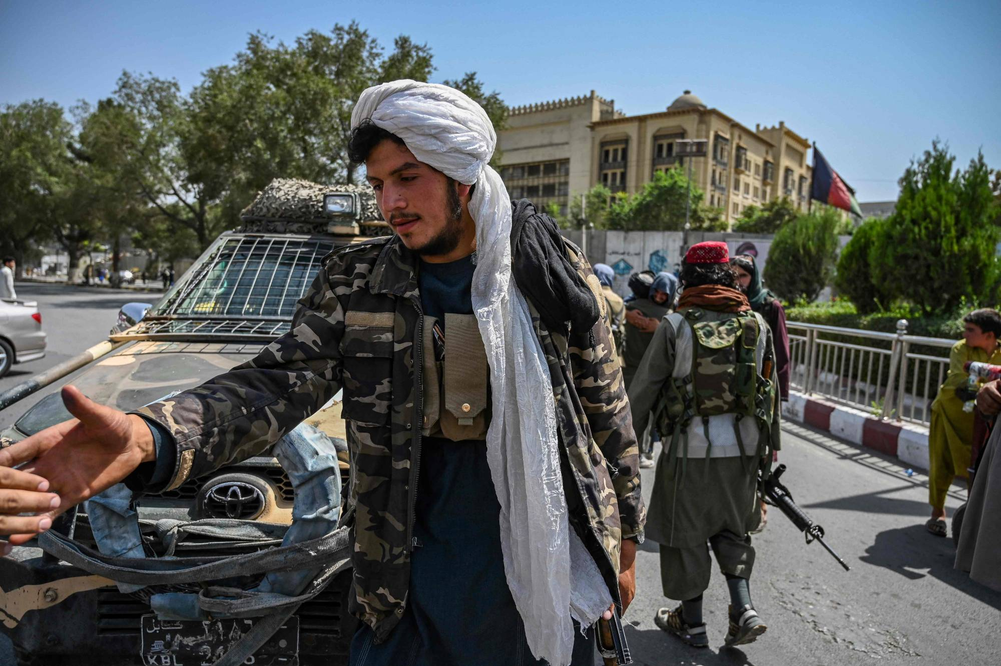 Taliban fighters stand guard along a street at the Kabul's Massoud Square on Monday. | AFP-JIJI