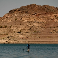 A paddle-boarder rides with a dog at the Lake Mead Marina on the Colorado River in Boulder City, Nevada on July 21. A huge reservoir that supplies water to tens of millions of people in the Western U.S. is at such a low level that populations it feeds must reduce their usage next year. | AFP-JIJI