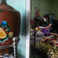 A volunteer treats a patient with COVID-19 at their home in the district of Taungoo, Myanmar.  | AFP-JIJI