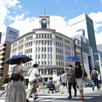 People walk in Tokyo's Ginza shopping district on Aug. 10. Economists believe the government will not be able to achieve the goal of restoring the economy to its prepandemic level by the end of this year. | KYODO