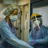 Nurses prepare to enter the room of a severely ill patient in the coronavirus ward at Itabashi Hospital in Tokyo in July.   RYUSEI TAKAHASHI