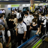 People walk out of a train in Shinjuku Station on Aug. 5. Prime Minister Yoshihide Suga asked businesses to reduce the number of commuters by 70% to cope with the continuing surge in COVID-19 infections.   AFP-JIJI