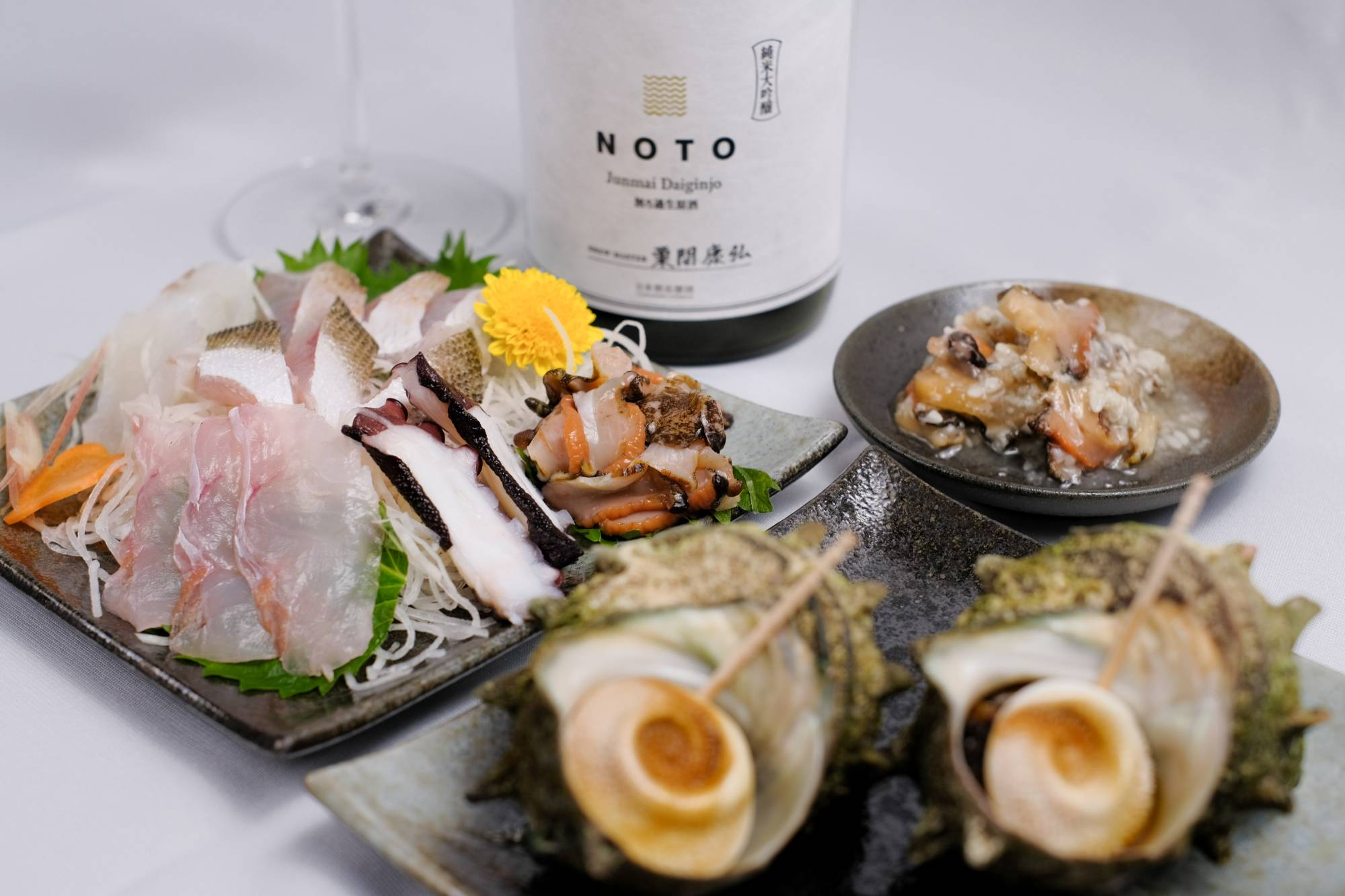 Nihonshu Oendan partners with regional producers to create food-and-sake pairing kits; August's offering comes with the brand's bright and juicy Noto sake from Ishikawa Prefecture, along with sazae (turban shell) prepared three ways and an assorted platter of five kinds of fresh fish from the Noto Peninsula.   NIHONSHU OENDAN INC, KOHEI ISHII