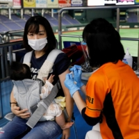 A woman receives a dose of a COVID-19 vaccine at Tokyo Dome, which is currently being used as a large-scale vaccination center.    REUTERS