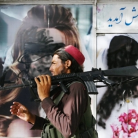A Taliban fighter on Wednesday walks past a beauty salon in Kabul with images of women defaced using spray paint.   AFP-JIJI