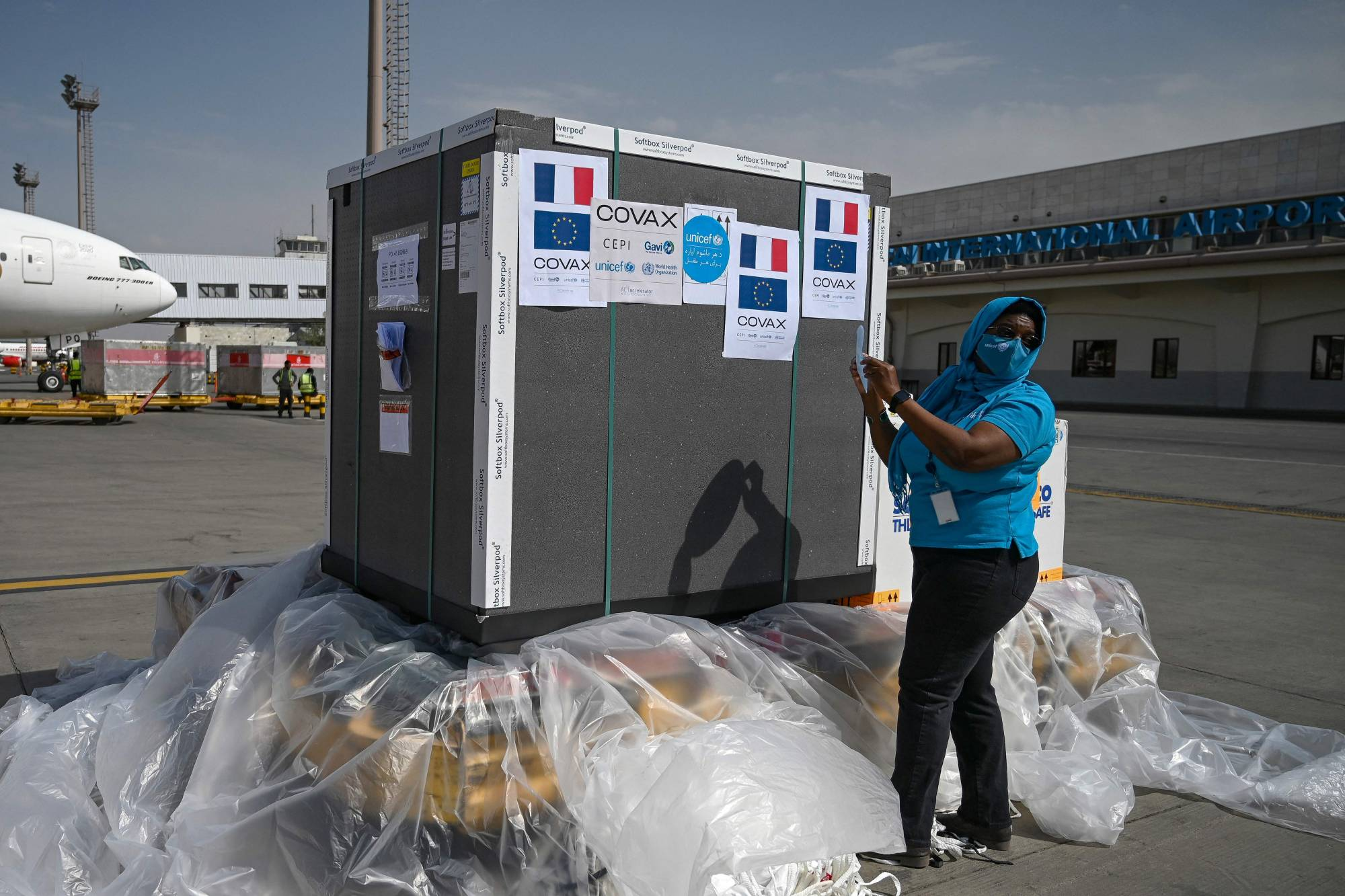 UNICEF members label a shipment of Astrazeneca COVID-19 vaccines donated by the French government after it arrived at Kabul Airport on Aug. 8.   AFP-JIJI