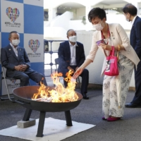 A woman puts a wooden strip with a message written on it into a fire during a lighting ceremony for the Paralympic torch relay in Tokyo's Koto Ward on Friday.   KYODO