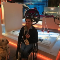Amanda McGrory poses in front of an exhibit featuring her racing wheelchair at the U.S. Olympic and Paralympic Museum in Colorado Springs, Colorado. | AMANDA MCGRORY