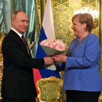 Russian President Vladimir Putin welcomes German Chancellor Angela Merkel during their meeting in Moscow. The trip will be the 20th and last visit to Russia for Angela Merkel as  Chancellor. | SPUTNIK / VIA AFP-JIJI