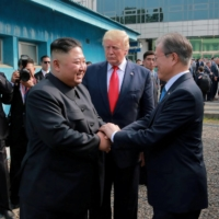 South Korean President Moon Jae-in shakes hands with North Korean leader Kim Jong Un at the demilitarized zone (DMZ) separating the two Koreas, in Panmunjom, South Korea, June 30, 2019. | REUTERS