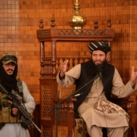An imam speaks next to an armed Taliban fighter during Friday prayers at the Abdul Rahman Mosque in Kabul on Friday. | AFP-JIJI