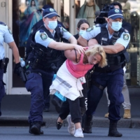 Police detain a protester in Sydney on Saturday following calls for an anti-lockdown protest rally amid a fast-spreading coronavirus outbreak. | AFP-JIJI