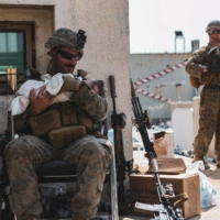 A U.S. Marine holds a baby during an evacuation at Hamid Karzai International Airport in Kabul on Thursday.    U.S. MARINE CORPS / VIA REUTERS
