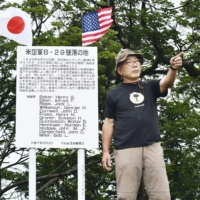Hiroshi Kudo next to a board in Takachiho, Miyazaki Prefecture, that commemorates a plane crash that killed 12 U.S. soldiers shortly after Japan surrendered in World War II.    KYODO