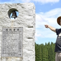 Hiroshi Kudo explains details of two plane crashes that killed U.S. soldiers and a Japanese pilot in August 1945, in front of a memorial stone in Takachiho, Miyazaki Prefecture.   KYODO