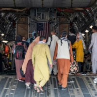 U.S. Air Force personnel assist evacuees at Kabul airport on Friday.    US AIR FORCE / VIA AFP-JIJI