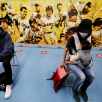 People wait for consultations after receiving a COVID-19 vaccine at Tokyo Dome on Monday. | REUTERS