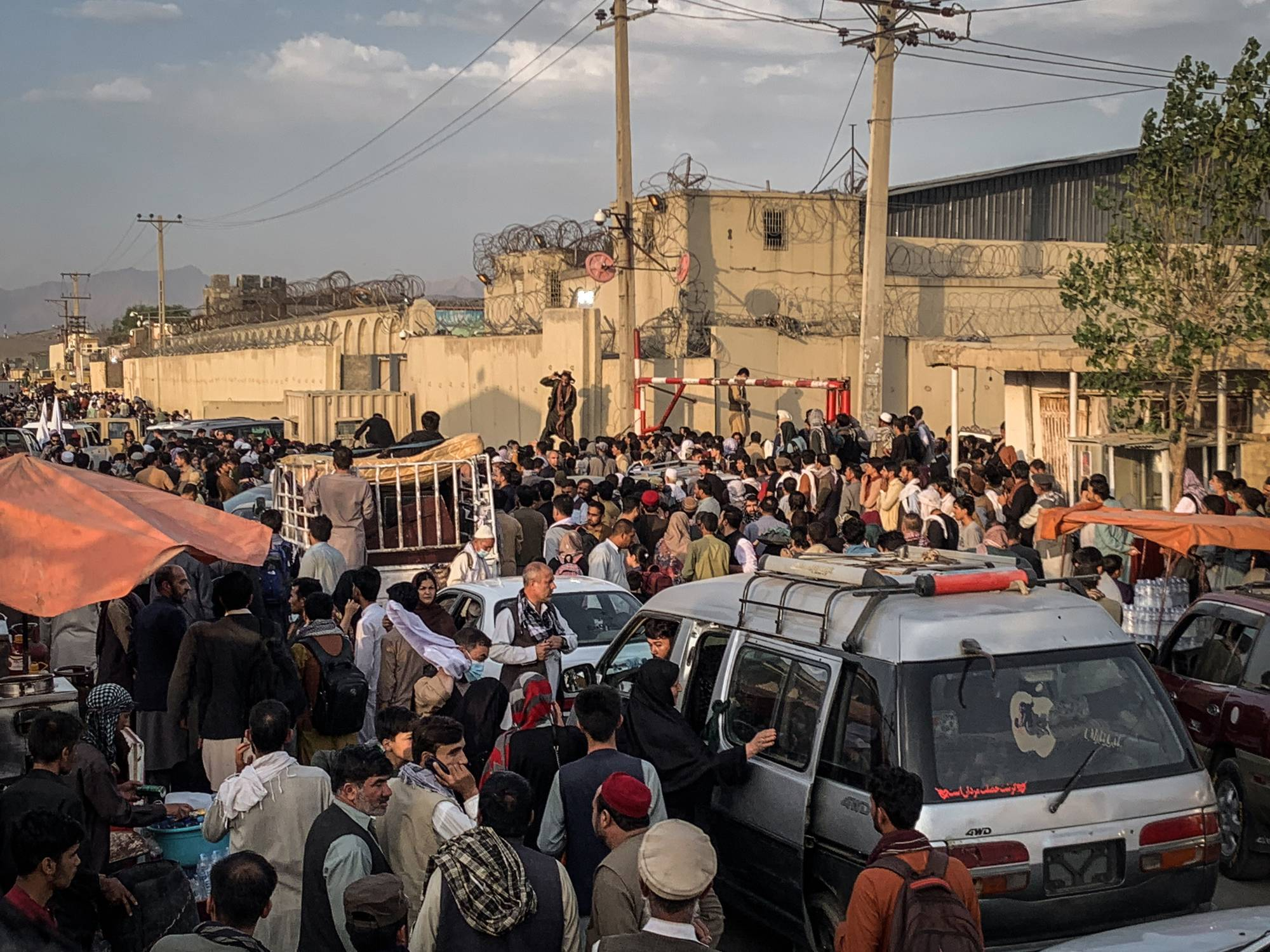 People gather near the airport in Kabul on Saturday.  | JIM HUYLEBROEK / THE NEW YORK TIMES
